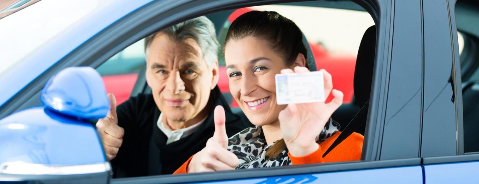 imatge d'una dona ensenyan el seu carnet de conduir amb l'examinador